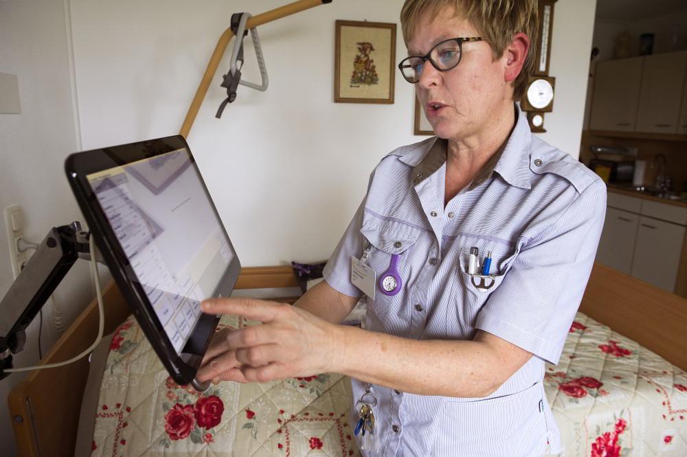 Medewerker van Vivantes met een aanraakscherm