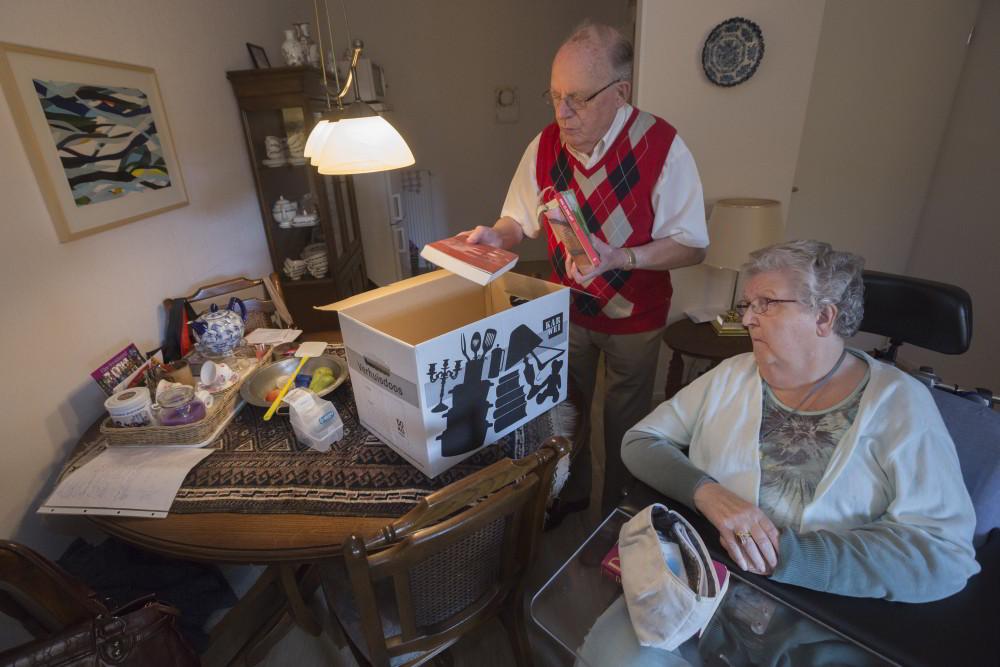 Ouderen pakken samen spullen in voor verhuizing naar verpleeghuis
