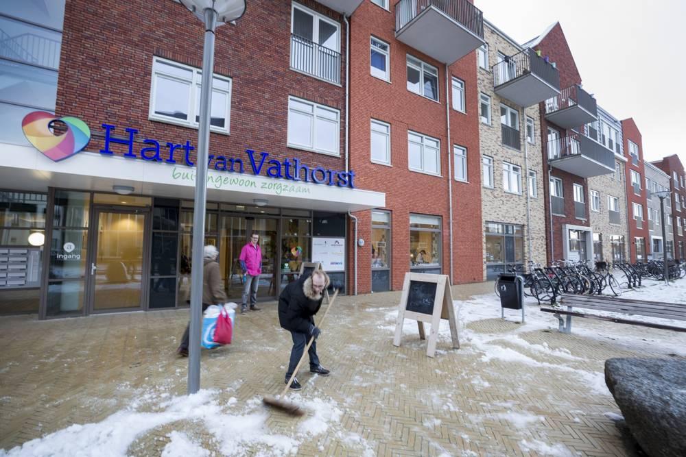 Hart van Vathorst - bewoner veegt de stoep voor de deur van de zorginstelling