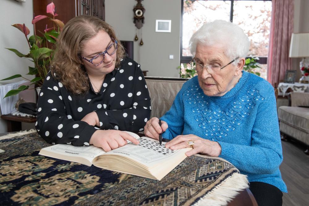 Vrouw met aandachtbaan maakt puzzel met bewoonster verpleeghuis