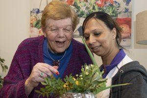 Professional met bewoner en bloemen bij WelThuis