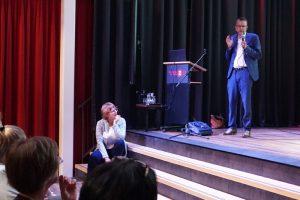 Man die spreekt op podium en vrouw zit naast podium