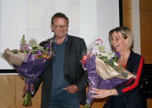 Man en vrouw met bos bloemen op podium