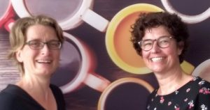 Twee lachende vrouwen met afbeelding koffiekopjes op achtergrond