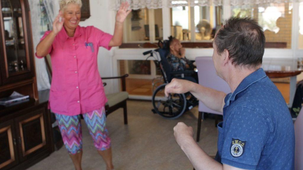 Verpleeghuisbewoner en verzorgende doen aan luchtdirigeren